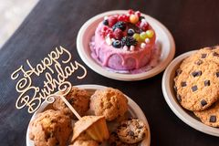 Κέικ και muffins γενεθλίων με το ξύλινο σημάδι χαιρετισμού στο αγροτικό υπόβαθρο Ξύλινος τραγουδήστε με τις επιστολές χρόνια πολλ Στοκ Εικόνες