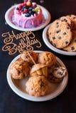 Κέικ και muffins γενεθλίων με το ξύλινο σημάδι χαιρετισμού στο αγροτικό υπόβαθρο Ξύλινος τραγουδήστε με τις επιστολές χρόνια πολλ Στοκ εικόνες με δικαίωμα ελεύθερης χρήσης