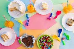 Κέικ, καραμέλα, σοκολάτα, συριγμοί, ταινίες, μπαλόνια, χυμός στον πίνακα διακοπών Έννοια της γιορτής γενεθλίων παιδιών ` s στοκ φωτογραφίες