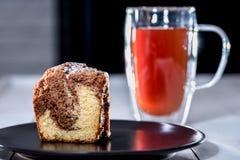 Κέικ καφέ σε ένα πιάτο με το τσάι στοκ εικόνες