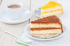 Κέικ καφέ στο άσπρο πιάτο στον ξύλινο πίνακα με τον καφέ και το ουρακοτάγκο Στοκ Εικόνες