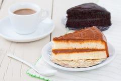 Κέικ καφέ στο άσπρο πιάτο στον ξύλινο πίνακα με τον καφέ και το choco Στοκ εικόνες με δικαίωμα ελεύθερης χρήσης