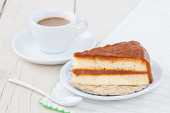 Κέικ καφέ στο άσπρο πιάτο στον ξύλινο πίνακα με τον καφέ Στοκ Φωτογραφίες