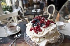 Κέικ μαρέγκας, εκλεκτής ποιότητας κουτάλια και δίκρανα, επιδόρπιο και καφές στο υπόβαθρο ενός εκλεκτής ποιότητας καφέ στοκ εικόνες με δικαίωμα ελεύθερης χρήσης