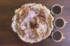 Κέικ μαρέγκας με τσιπ σοκολάτας και τρία φλιτζάνια του καφέ Στοκ εικόνα με δικαίωμα ελεύθερης χρήσης