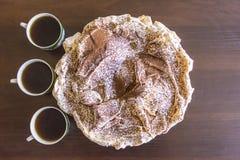 Κέικ μαρέγκας με τσιπ σοκολάτας και τρία φλιτζάνια του καφέ Στοκ Εικόνες