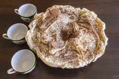 Κέικ μαρέγκας με τσιπ σοκολάτας και τρία φλυτζάνια καφέ Στοκ φωτογραφία με δικαίωμα ελεύθερης χρήσης