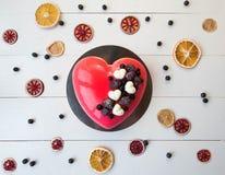 Κέικ με μορφή μιας καρδιάς σε ένα άσπρο ξύλινο υπόβαθρο Στοκ Φωτογραφία