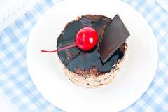 Κέικ με τα κεράσια και σοκολάτα, Cupcake στο ξύλο Στοκ Φωτογραφία