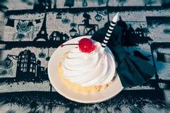 Κέικ με την κρέμα και τα κεράσια, κερί, δεσμός τόξων στοκ φωτογραφία με δικαίωμα ελεύθερης χρήσης