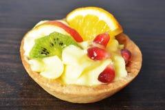 Κέικ με την κρέμα και φρούτα σε ένα καλάθι στοκ εικόνα