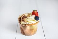 Κέικ με την κρέμα και ψεκασμένος με το κακάο, και φράουλες και βακκίνια Στοκ Εικόνες