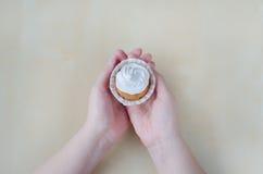 Κέικ με την κρέμα στα χέρια γυναικών Στοκ Εικόνες