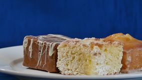 Κέικ με το κεράσι σε ένα άσπρο πιάτο στους ξύλινους πίνακες Διαφορετικές ζύμες κέικ απόθεμα βίντεο