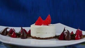 Κέικ με το πάγωμα και τα σμέουρα μαρέγκας Κέικ Pavlova μαρεγκών με το φρέσκα σμέουρο και το βακκίνιο σε έναν σκούρο μπλε απόθεμα βίντεο
