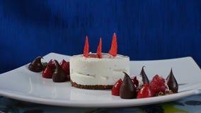 Κέικ με το πάγωμα και τα σμέουρα μαρέγκας Κέικ Pavlova μαρεγκών με το φρέσκα σμέουρο και το βακκίνιο σε έναν σκούρο μπλε Στοκ Φωτογραφίες