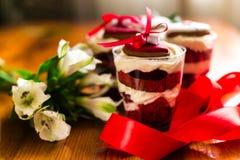 Κέικ μικροπράγματος στον πίνακα με την κόκκινα κορδέλλα και τα λουλούδια στοκ φωτογραφίες
