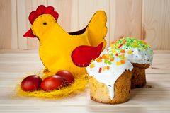 Κέικ Πάσχας και χρωματισμένα αυγά με το κοτόπουλο Πάσχας σε έναν ξύλινο πίνακα στοκ εικόνα
