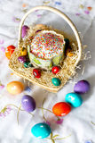 Κέικ Πάσχας με το λούστρο ζάχαρης και ζωηρόχρωμα - κίτρινος, κόκκινος, ιώδης, πράσινος, βιολέτα - αυγά Πάσχας με τις άσπρες εικόν Στοκ Εικόνες