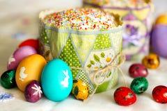 Κέικ Πάσχας με το λούστρο ζάχαρης και ζωηρόχρωμα - κίτρινος, κόκκινος, ιώδης, πράσινος, βιολέτα - αυγά Πάσχας με τις άσπρες εικόν Στοκ εικόνα με δικαίωμα ελεύθερης χρήσης