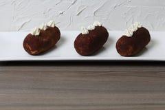 Κέικ πατατών Διακοσμημένος με τα λουλούδια κρέμας Σε ένα άσπρο ορθογώνιο πιάτο Στα πλαίσια του άσπρου τοίχου με διακοσμητικό στοκ φωτογραφία