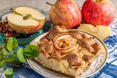 Κέικ πιτών της Apple στο πιάτο με τα φρέσκα κόκκινα μήλα Διάσημος ξινός με τους διαφορετικούς τύπους συνταγών Στοκ εικόνα με δικαίωμα ελεύθερης χρήσης