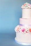 Κέικ που διακοσμείται με τα λουλούδια σε ένα μπλε υπόβαθρο Στοκ Εικόνες