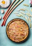 Κέικ ρεβεντιού Ψημένη σπιτική πίτα με το ρεβέντι στο μπλε επιτραπέζιο υπόβαθρο κουζινών με τα συστατικά στοκ εικόνα με δικαίωμα ελεύθερης χρήσης