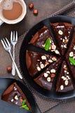 Κέικ σοκολάτας με την καυτή σάλτσα σοκολάτας και τα τηγανισμένα φουντούκια στοκ εικόνες