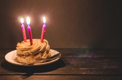 Κέικ σοκολάτας με την κρέμα και τρία καίγοντας κεριά σε ένα σκοτεινό υπόβαθρο Στοκ Εικόνες