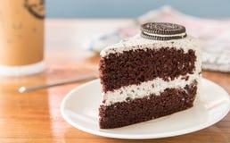 Κέικ σοκολάτας με το oreo και κτυπημένη κρέμα στο άσπρο πιάτο και wo στοκ εικόνες