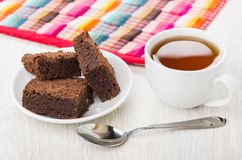Κέικ σοκολάτας στο πιατάκι, την πετσέτα, το φλυτζάνι του τσαγιού και το κουταλάκι του γλυκού Στοκ Εικόνες