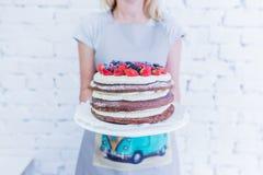 Κέικ σοκολάτας whoopie στο πιάτο με τα φρέσκα μούρα, κράτημα χεριών γυναικών ` s Στοκ Εικόνες