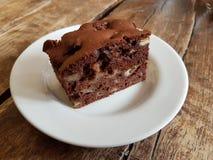 Κέικ σοκολάτα-Apple σε ένα πιάτο Γλυκό επιδόρπιο σε ένα άσπρο πιάτο που εγκαθίσταται σε έναν ξύλινο πίνακα Στοκ φωτογραφίες με δικαίωμα ελεύθερης χρήσης
