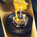 Κέικ σοκολάτας με ένα κερί και τα δώρα Χρόνια πολλά, κάρτα Ευχετήρια κάρτα διακοπών Στοκ Εικόνα