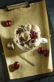 Κέικ σοκολάτας με τα κεράσια και ένα φλιτζάνι του καφέ με την κτυπημένη κρέμα croissant γλυκό φλυτζανιών καφέ σπασιμάτων ανασκόπη Στοκ Φωτογραφίες