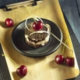 Κέικ σοκολάτας με τα κεράσια και ένα φλιτζάνι του καφέ με την κτυπημένη κρέμα croissant γλυκό φλυτζανιών καφέ σπασιμάτων ανασκόπη Στοκ Φωτογραφία