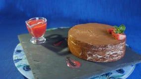 Κέικ σοκολάτας με τη φράουλα, ένα σκούρο μπλε υπόβαθρο, κέικ με τρία στρώματα του διαφορετικού γούστου, γλυκά Υψηλός - ποιότητα απόθεμα βίντεο