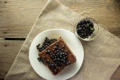 Κέικ σοκολάτας με το βακκίνιο και γυαλί με τα μούρα Στοκ Φωτογραφίες