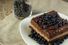 Κέικ σοκολάτας με το βακκίνιο και γυαλί με τα μούρα Στοκ Εικόνες