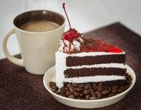 Κέικ σοκολάτας σε ένα άσπρους πιάτο και έναν καφέ Στοκ Εικόνες