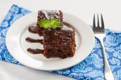 Κέικ σοκολάτας σε ένα πιάτο για το φοντάν, και μπλε πετσέτα Στοκ φωτογραφία με δικαίωμα ελεύθερης χρήσης