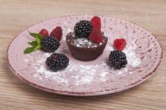 Κέικ σοκολάτας σε ένα πιάτο με τα σμέουρα και τα βατόμουρα Στοκ Φωτογραφία