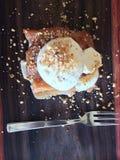 Κέικ στο σκούρο κόκκινο ξύλινο πιάτο και το στιλπνό δίκρανο μετάλλων Στοκ εικόνες με δικαίωμα ελεύθερης χρήσης