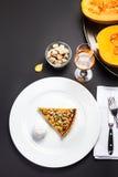 Κέικ στρώματος σοκολάτας με την καραμέλα, τα καρύδια και τη σοκολάτα στο άσπρο π Στοκ Φωτογραφία