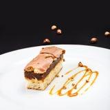 Κέικ στρώματος σοκολάτας με την καραμέλα, τα καρύδια και τη σοκολάτα στο άσπρο π Στοκ Εικόνες