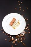 Κέικ στρώματος σοκολάτας με την καραμέλα, τα καρύδια και τη σοκολάτα στο άσπρο π Στοκ φωτογραφία με δικαίωμα ελεύθερης χρήσης
