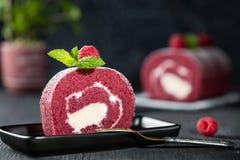 Κέικ σφουγγαριών ελβετικών ρόλων με τη φρέσκια τήξη σμέουρων, μεντών και ζάχαρης στο σκοτεινό υπόβαθρο Στοκ Εικόνες