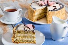Κέικ σφουγγαριών με τους σπόρους παπαρουνών με ένα αποκόπτω κομμάτι Στοκ Φωτογραφίες