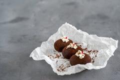 Κέικ φιαγμένα από σοκολάτα σε άσπρο διαφανές χαρτί για ένα γκρίζο υπόβαθρο Κέικ που διακοσμούνται με την κόκκινη ζελατίνα και τη  Στοκ φωτογραφία με δικαίωμα ελεύθερης χρήσης